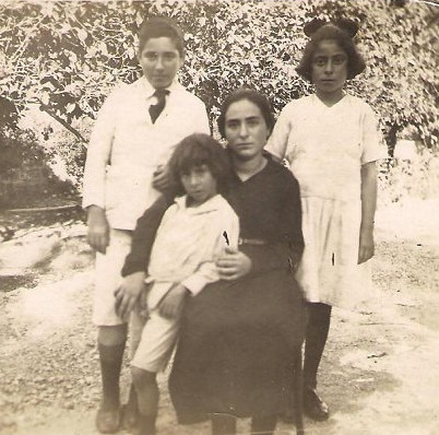 'Abdu'l-Baha's Shahid family grandchildren. Left to right standing at back: Munib Shahid and Zahra Shahid. Standing front: Hassan Jalal Shahid. Sitting front: Maryam Shahid.